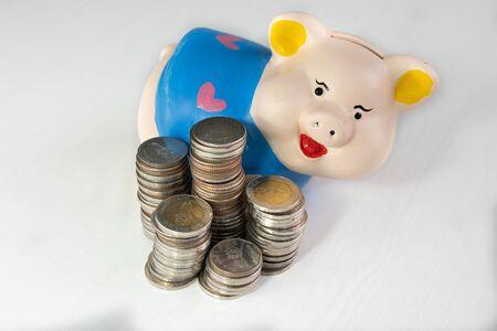 Photo pour saving money with Blue piggy bank and coins pile. - image libre de droit