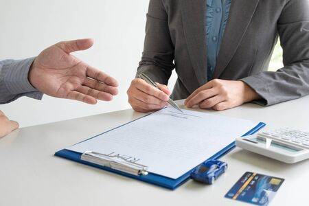 Photo pour Car dealership provides advice about insurance details and car rental information and delivers the keys after signing the rental contract. - image libre de droit