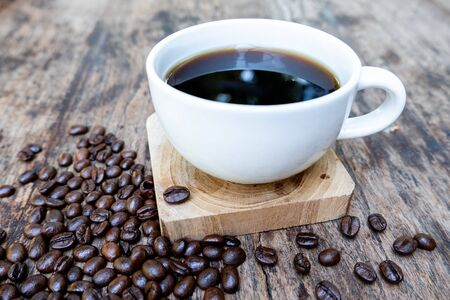 Photo pour full of coffee beans spilling out bag on brown wooden background with a cup of black coffee. - image libre de droit