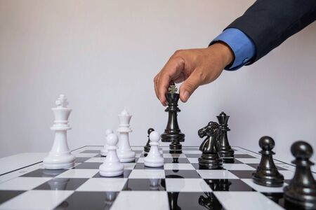 Photo pour hand of businessman moving chess in competition, shows leadership, followers and business success strategies. - image libre de droit