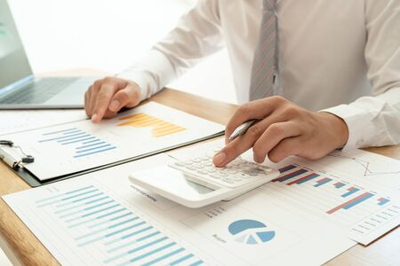 Photo pour A business man is sitting at a desk and calculating financial graphs about real estate investment expenditures. - image libre de droit