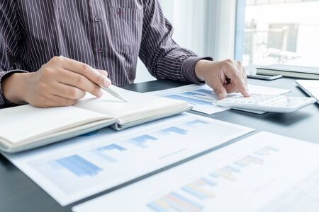 Photo pour The hands of a male businessman are analyzing and calculating the annual income and expenses in a financial graph that shows results To summarize balances overall in office. - image libre de droit
