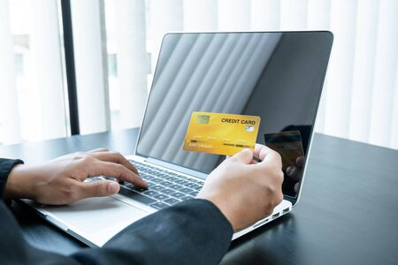 Photo pour The businesswoman's hand is holding a credit card and using a smartphone for online shopping and internet payment in the office. - image libre de droit