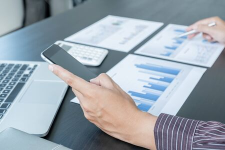Photo for The hands of a male businessman are analyzing and calculating the annual income and expenses in a financial graph that shows results To summarize balances overall in office. - Royalty Free Image