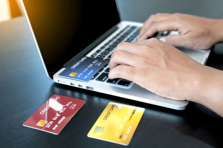 Photo pour The businessman's hand is holding a credit card and using a laptop for online shopping and internet payment in the office. - image libre de droit