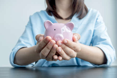 Photo pour A woman's hand holds a piggy bank for saving into a growing business to succeed and save for retirement. - image libre de droit