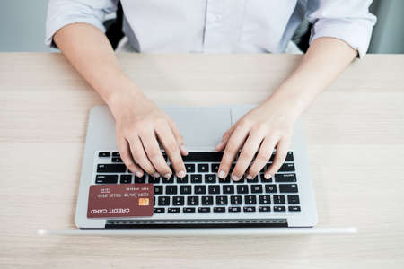 Photo pour The businesswoman's hand is holding a credit card and using a laptop for online shopping and internet payment in the office. - image libre de droit