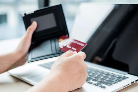 Foto de The businesswoman's hand is holding a credit card and using a laptop for online shopping and internet payment in the office. - Imagen libre de derechos