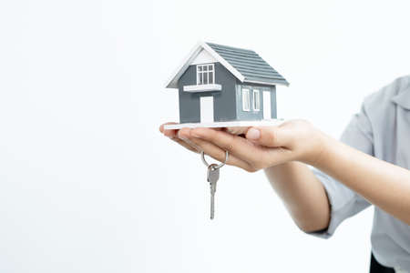 Photo pour The hand of the real estate agent holding the house model and the keys Loan and home concept. - image libre de droit