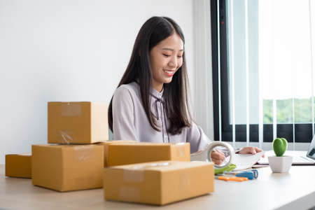 Photo pour Young Asian woman business owner with many parcel boxes on the table happy online sales job, use your laptop, get an order from customers, take notes, and make arrangements for delivery by post. - image libre de droit