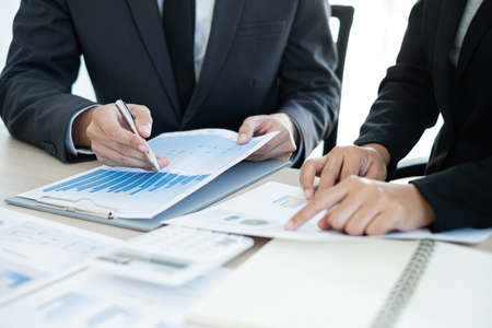 Foto de Two business leaders talk about charts, financial graphs showing results are analyzing and calculating planning strategies, business success building processes. - Imagen libre de derechos