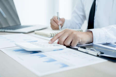 Photo for The businessman hand sits at their desks and calculates financial graphs showing the results of their investments planning the process of successful business growth. - Royalty Free Image
