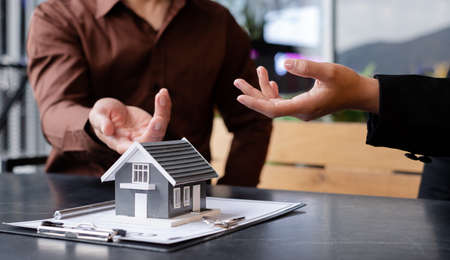 Photo pour A real estate agent with a House model is talking to clients about buying home insurance. Home insurance concept. - image libre de droit