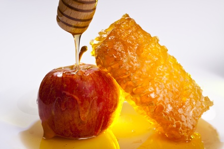 red apple with honeycomb and pooring honey on it white backgroundの写真素材