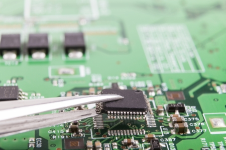 Mounting microchip on electronic circuit board with tweezers