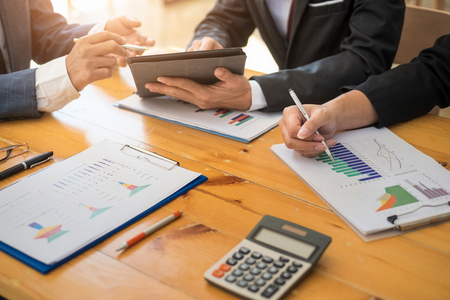 Photo pour Group of business people working with laptop and tablat and paper graph in the office room. Accounting concept. - image libre de droit