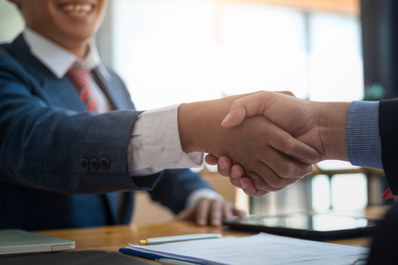 Business real estate broker and customer shaking hands after signing a contract housing estate in office. contract and agreement concept.