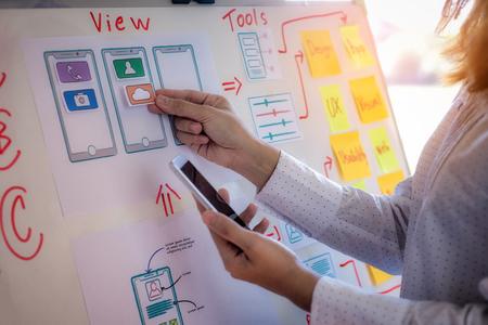 Photo pour Web designer woman doing test sketch drawing application for mobile phone in office. User experience Design concept. - image libre de droit