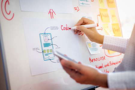 Photo pour Closeup hand of designer woman sort layout of drawing application for developing for mobile applications. User experience Design concept. - image libre de droit