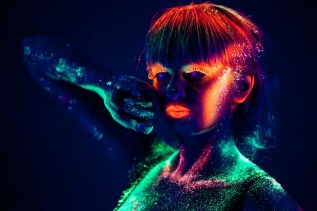 Woman s face with fluorescent bodyart  Black background  Studio shot