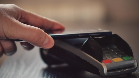 Foto de Hand with a smart phone using the terminal for payment by NFC technology - Imagen libre de derechos