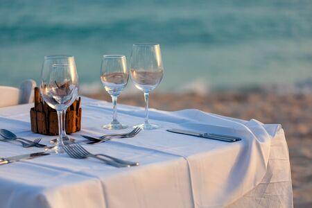 Photo pour Serving for romantic dinner on a beach at sunset - image libre de droit