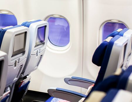 Photo pour Aircraft interior with seats and blank touch screens displays. - image libre de droit