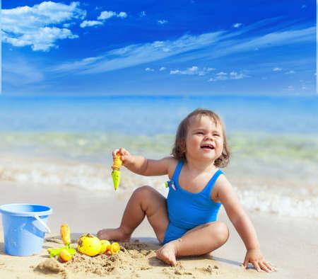 Photo pour Happy smiling little child girl playing on a sea beach - image libre de droit