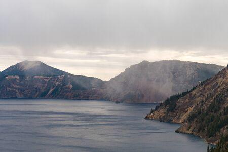 A storm cloud discharging water over Crater Lake, Oregon, USA