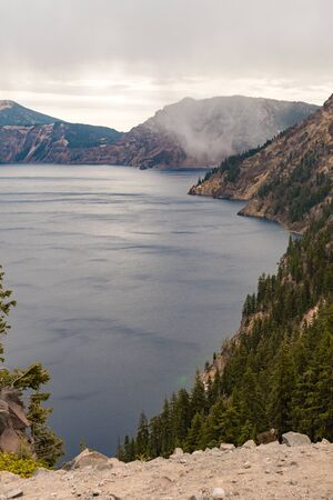 A storm cloud discharging water over Crater Lake