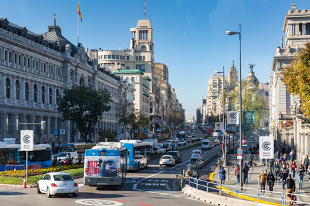 Madrid, Spain - November 29, 2018: Rush-hour on the Calle de Acala traffic circle Paseo del Prado, with cars, buses, pedestrians and motorbikes.
