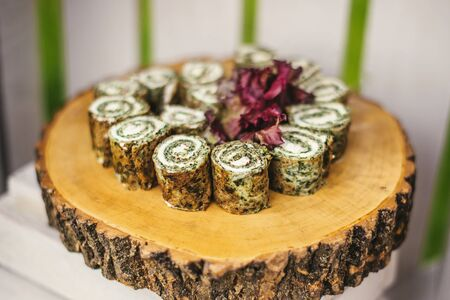 Roll with spinach, sliced on wooden stump