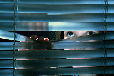Girl's eyes looking through window blinds