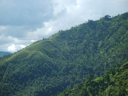 A green mountain and a cloudy sky, dividing the photo diagonally