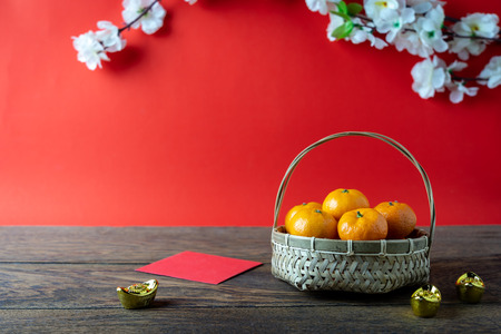 Foto de Accessories on Lunar New Year & Chinese New Year vacation concept background.Orange in wood basket with  red pocket money and flower on modern rustic brown & red backdrop at home office desk studio. - Imagen libre de derechos