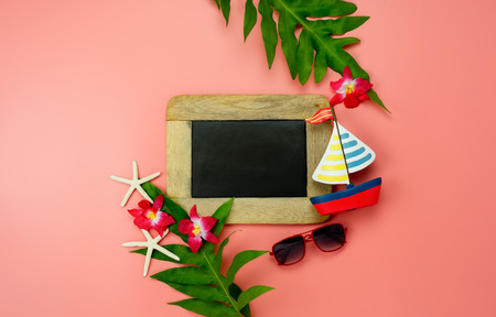 Foto de Table top view accessory plan to travel beach in summer holiday background concept.Flat lay  palm leaf with many essential items flower & sunglasses on pink paper.Blackboard for design text - Imagen libre de derechos