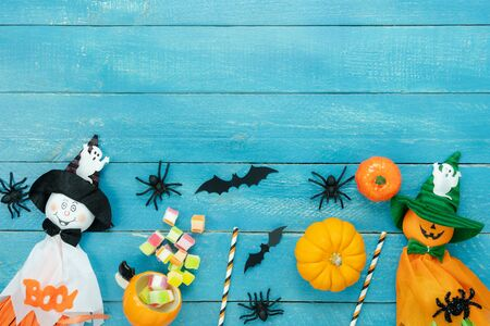 Photo pour Table top view aerial image of decoration Happy Halloween day background concept.Flat lay accessories essential object to party the pumpkin & doll and candy on blue wooden.Space for creative design. - image libre de droit