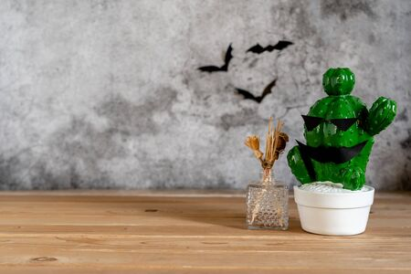 Foto de Accessories of decorations Happy Halloween day background concept.Jack O Lanterns cactus with spooky pumpkins object to party season with spider on modern rustic brown & white stone backdrop. - Imagen libre de derechos