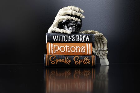 Photo pour Halloween Skeleton hands holding magic books for Halloween - image libre de droit