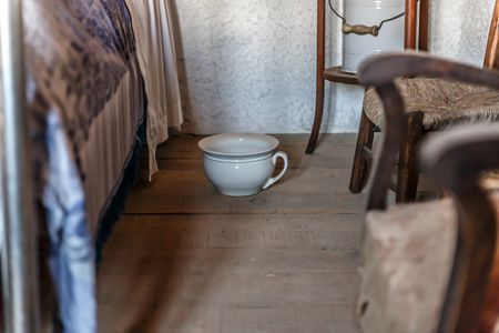 Old white urinal placed next to a bed in a bedroom in an old house