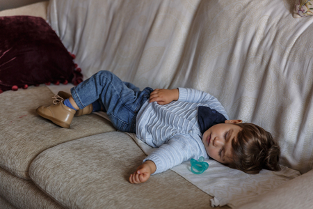 Photo pour Cute boy dressed in blue, rests peacefully on sofa in the living room of his house - image libre de droit