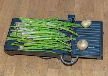 Kitchen griddle with a large bunch of tender green asparagus and two fresh onions