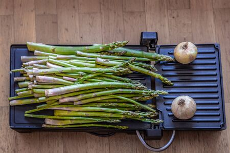 Large bunch of green and fresh asparagus placed on a grill next to two onions, ready for roasting