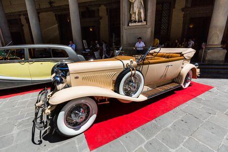FLORENCE, ITALY - JULY 17, 2016: View of a public outdoor oldtimer car exhibition at the Piazzale degli Uffizi on July, 17, 2016. Rare car were shown to the public in the hearth of Florence in Italy.