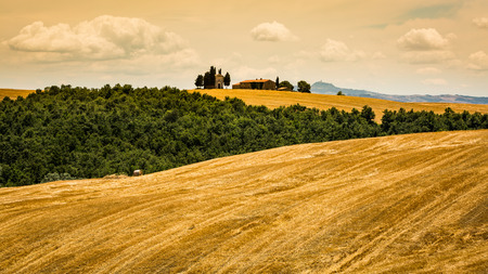 SAN QUIRICO D ORCIA, ITALY - JULY 16, 2016: View of a farm house and church in the tuscan region San Quirico d Orcia in Italy on July 16, 2016. This region is popular for tuscan style photographic motives.