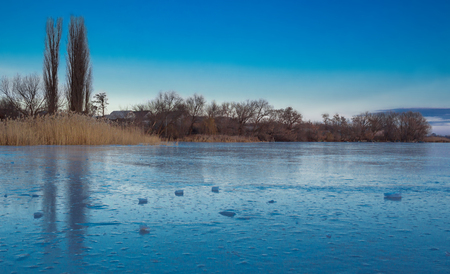 Winter paysage landscape of frozen village on iced lake river under snow