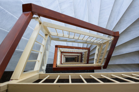 Perspective view down to spiral geometrical stairway of marble steps and wooden rails