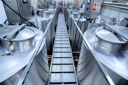 Photo pour Equipment at modern dairy plant with stainless tanks - image libre de droit