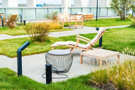 Foto de Modern rooftop patio with wooden armchair during the day - Imagen libre de derechos