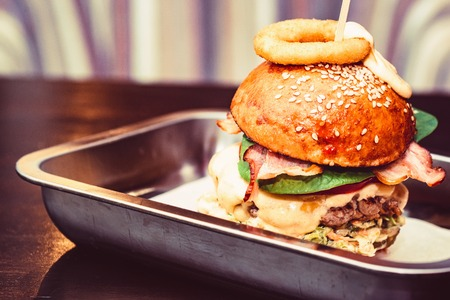 Photo pour Close up tall tasty burger with cheese served on tray - image libre de droit